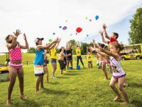 kids playing balloon toss outdoor party entertainment