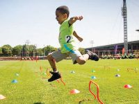 boy jumping over hurdles at sports day outdoor party entertainment