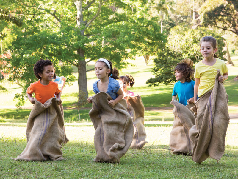 kids playing sack races at birthday party
